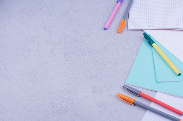 Papeles en blanco y lápices de colores sobre superficie gris