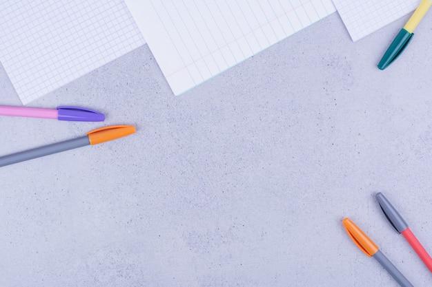 Papeles en blanco y lápices multicolores sobre gris.