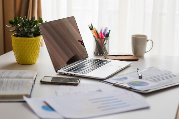 Papeles y computadora portátil en la mesa de oficina