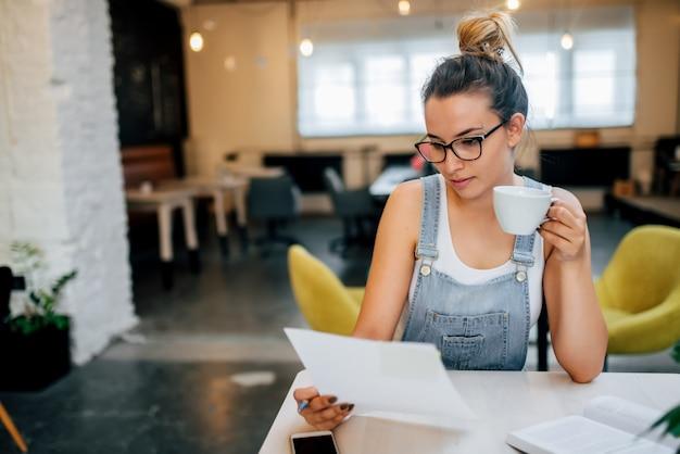 Papeles de examen del empresario joven pensativo mientras que se sienta en la tabla en cafetería.