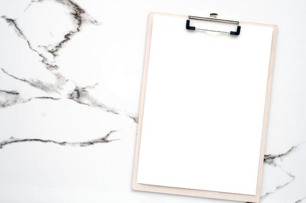 Papeles de nota blanca en blanco y portapapeles sobre mármol blanco