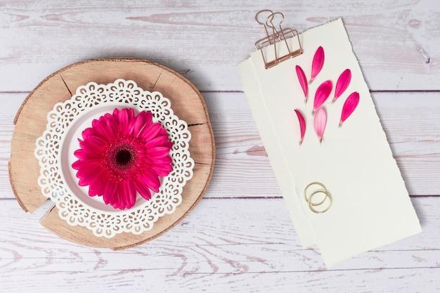 Papeles con pétalos y anillos cerca de flor en madera redonda