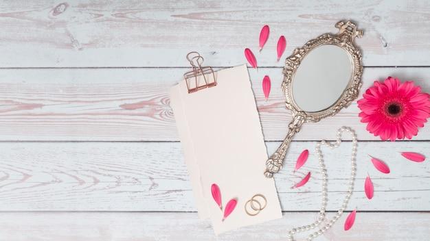 Papeles con pétalos cerca de flor, anillos y espejo.