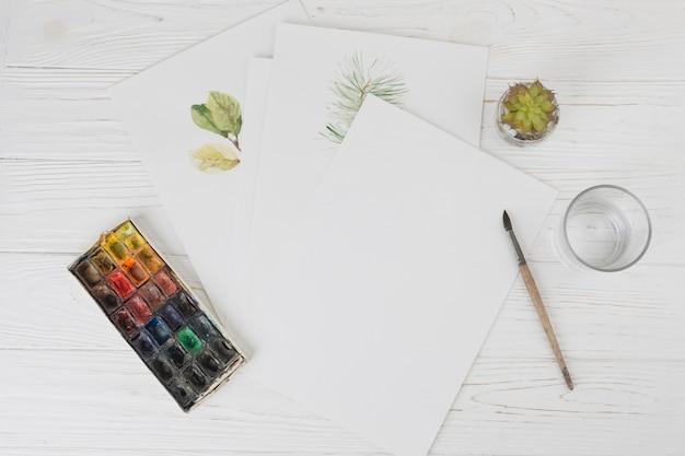 Papeles con pinturas para plantas cerca de vidrio, brocha y un conjunto de colores de agua