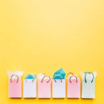 Papeles tisú en la fila de bolsas de compra dispuestas sobre fondo amarillo
