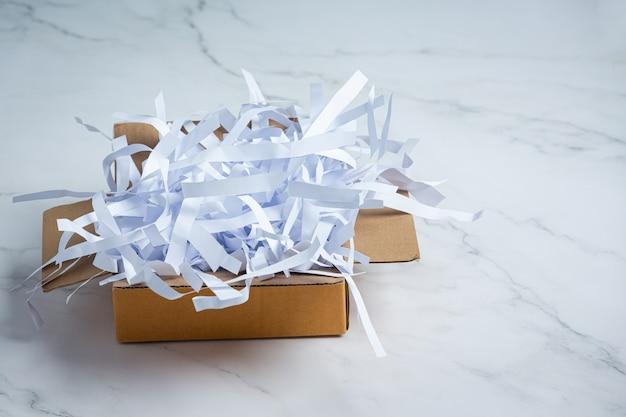 Papeles usados y cajas de cartón colocadas sobre suelo de mármol blanco