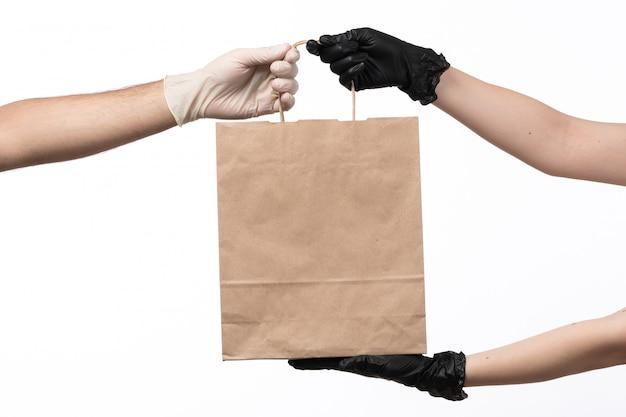Un paquete de alimentos de papel de vista frontal entregando de mujer a hombre en blanco