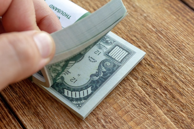Paquete de billetes y monedas en dólares con la mano