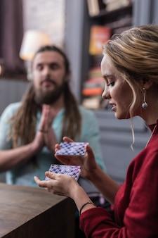 Paquete de cartas del tarot. agradable joven barajando las cartas del tarot mientras piensa en su destino