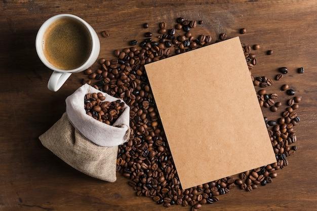 Paquete cerca de taza y saco con granos de café.