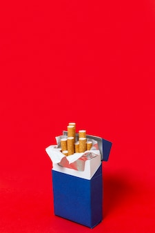 Paquete de cigarrillos azules sobre fondo rojo.