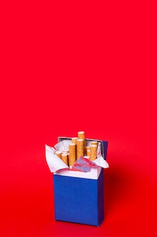 Paquete de cigarrillos sobre fondo rojo.