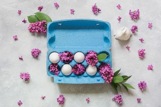 Paquete creativo de huevos con conejo y flores decorativas lilas fondo claro. concepto de pascua.