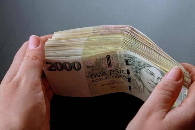 Paquete de dinero checo en manos de una mujer sobre un fondo negro