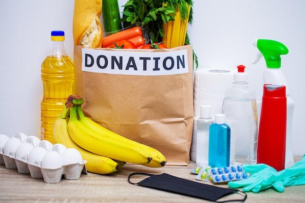 Paquete de donación con alimentos y equipo de protección personal para personas necesitadas