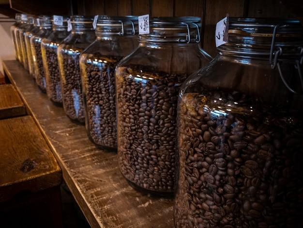 Paquete de empaquetado del tarro de cristal de los granos de café negro en el soporte de madera en el fondo de la tienda del café. haba de café recién tostado en botella de la casa.