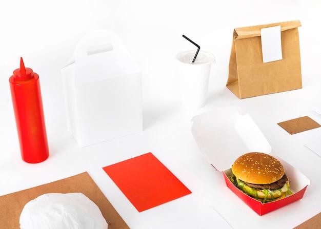 Paquete; hamburguesa; maqueta de salsa y vaso desechable sobre fondo blanco