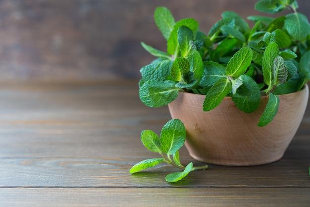 Paquete de hierbabuena fresca menta aislado en la pared de madera. hojas de menta verde manojo de menta en un tazón, hojas de hierba en la mesa de madera.