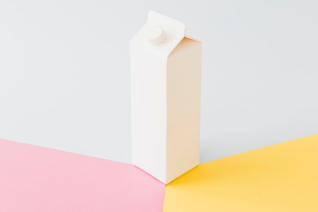 Paquete de leche de cartón blanco en tablero brillante
