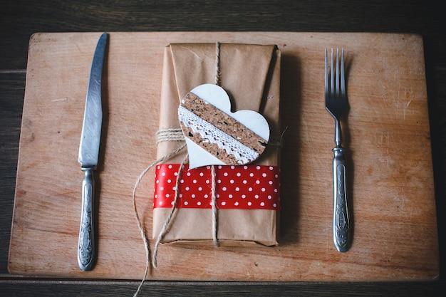 Paquete marrón con un corazón y cubiertos a los lados