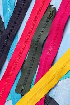 Paquete de muchas cremalleras de plástico y metal a rayas de colores con deslizadores