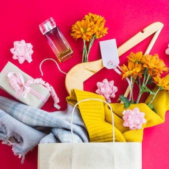 Paquete de papel artesanal con las compras de las mujeres - ropa, regalos, perfumes, flores