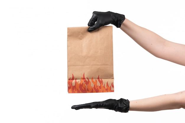 Un paquete de papel de vista frontal vacío espera por hembra en guantes negros sobre blanco