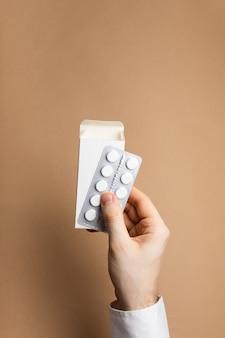 Paquete de pastillas en maqueta de manos masculinas
