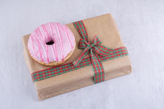 Paquete de regalo y un donut glaseado sobre superficie blanca
