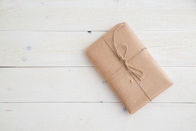 Paquete, regalo embalado en papel ecológico sobre fondo de madera clara. la vista desde arriba