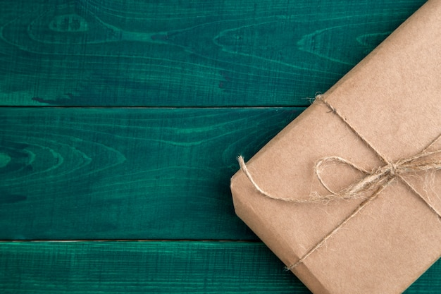 Paquete, regalo embalado en papel ecológico sobre fondo de madera verde oscuro. la vista desde arriba