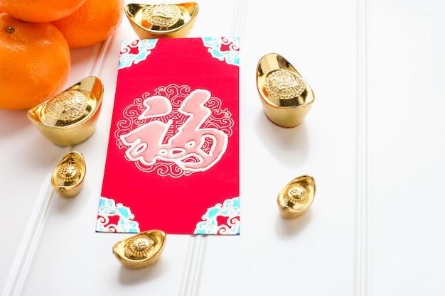 Paquete de sobres rojos del año nuevo chino (pow ang) con lingotes de oro y mandarina en la mesa