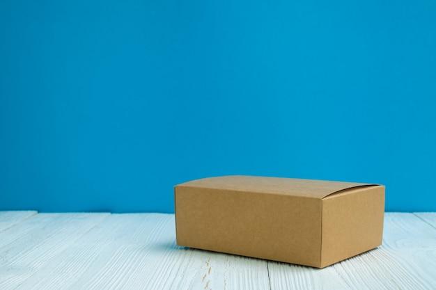 Paquete vacío vacíe la caja o la bandeja de cartón marrón en la mesa de madera blanca brillante con el fondo azul de la pared.