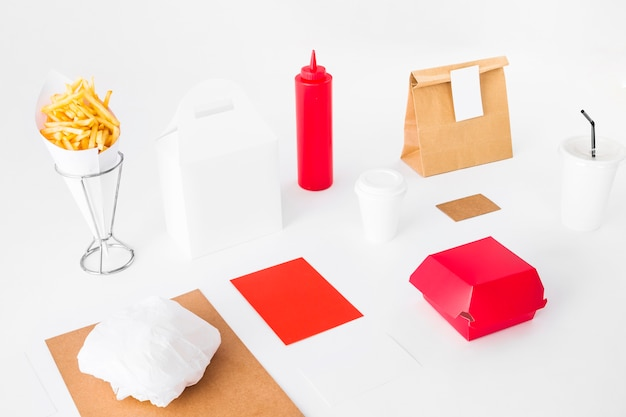 Paquetes de comida con papas fritas y vaso desechable sobre fondo blanco