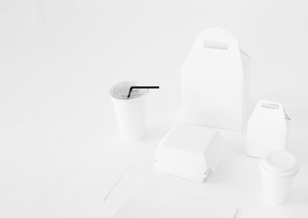 Paquetes de comida y taza de eliminación en mesa blanca