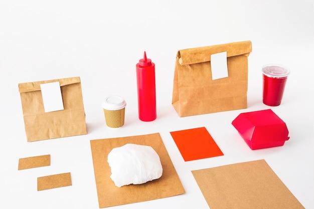 Paquetes de comida con vaso de basura y botella de salsa sobre fondo blanco