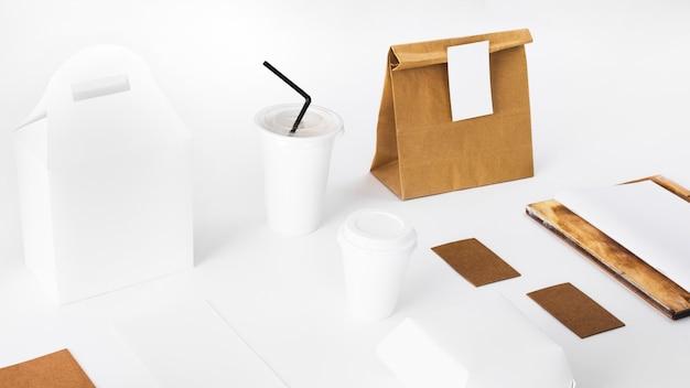 Paquetes de comida y vaso de disposición sobre superficie blanca.