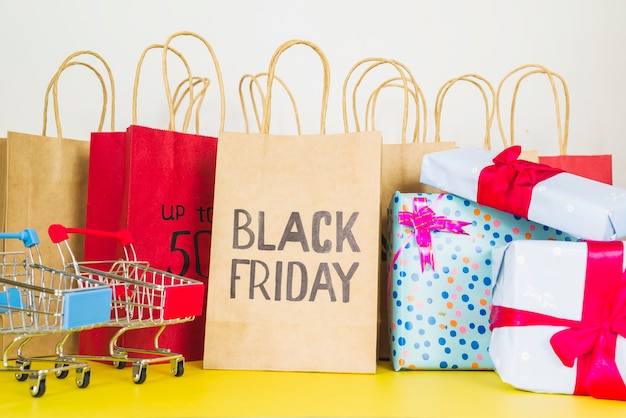Paquetes de compras cerca de carritos de supermercado y cajas de regalo.