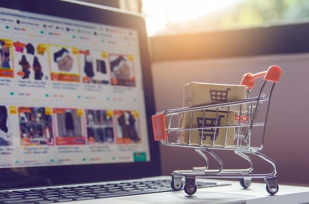 Paquetes o paquetes de papel con el logotipo de un carrito de compras en un carrito en un teclado de computadora portátil.