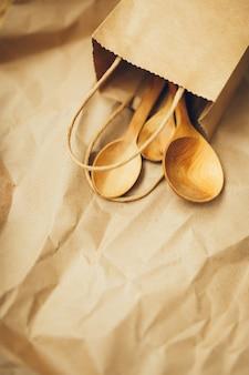 Paquetes de papel con cucharas de madera sobre fondo marrón