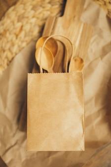 Paquetes de papel con las cucharas y la tabla de cortar de madera en fondo marrón. copia espacio vista superior. eco y concepto de salvar la tierra. cero desperdicio.