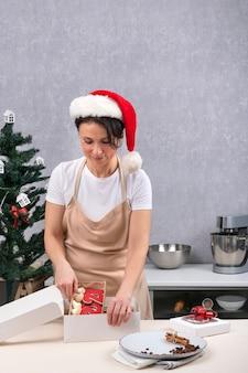 Paquetes de repostería caja de regalo con sabrosos dulces navideños. retrato de mujer con sombrero de año nuevo en la cocina. marco vertical.
