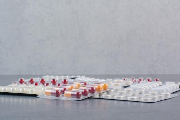 Paquetes surtidos de medicamentos en superficie de mármol.