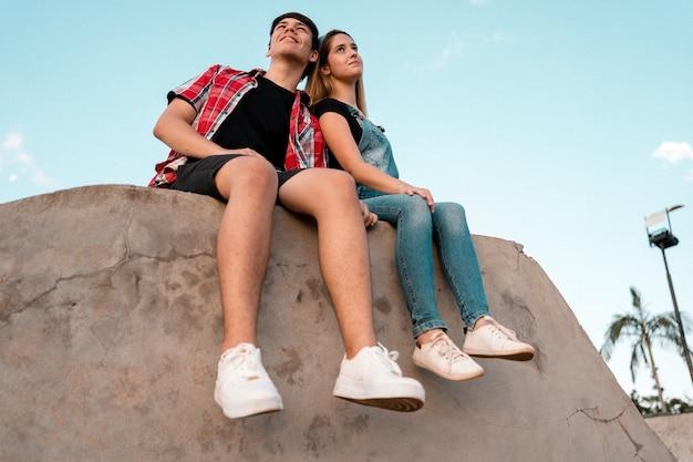 Par de adolescentes sentados en un parque de la ciudad