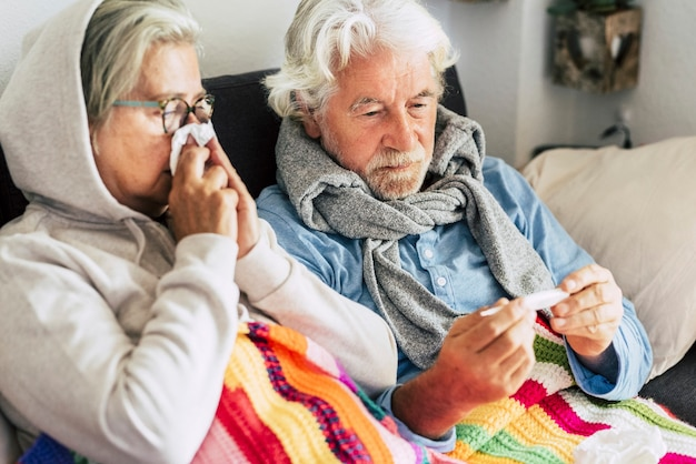 Par de ancianos enfermos y personas maduras sentados en el sofá con fiebre mirando el termómetro con alta temperatura