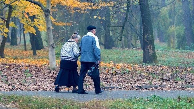 Un par de ancianos, marido y mujer, caminando en el parque de otoño