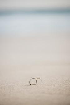 Par de anillo de bodas en la arena