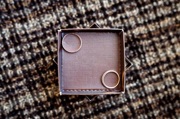 Un par de anillos de boda en una caja de madera. decoración de boda. símbolo de familia, unidad y amor.