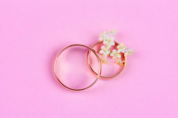 Un par de anillos de bodas de oro y pequeñas flores blancas en un anillo.