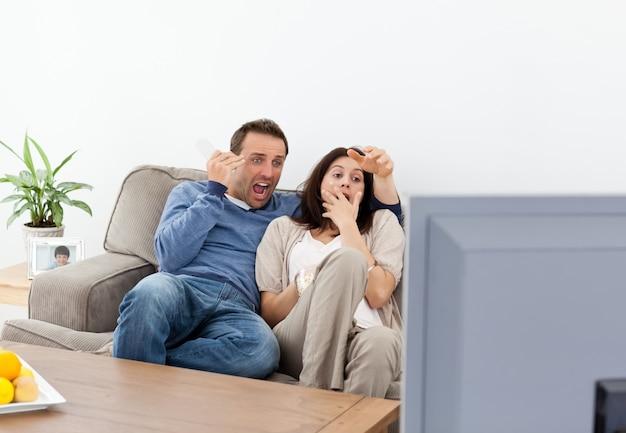 Par asustado viendo una película de terror en la televisión